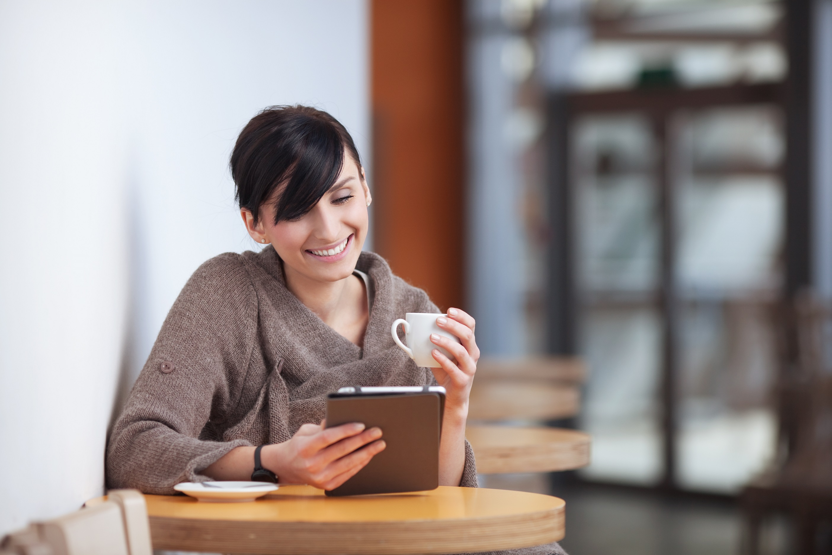 Young happy woman sitting in the restaurant with digital tablet, drinking coffee